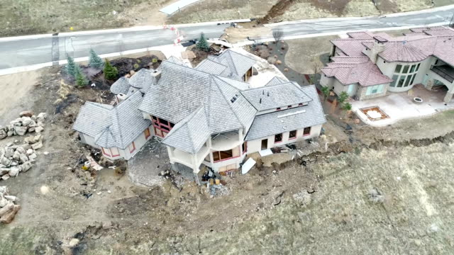 Aerial view of a home falling apart as the land below slides video