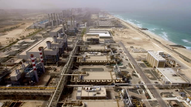 Aerial view of a huge power plant on the shore of the sea in Dubai, UAE video