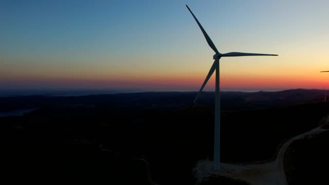 Aerial view of a white big windmill at colorful sunset video