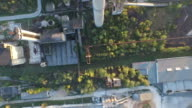 Aerial view of abandoned industrial buildings and chimney at sunset video