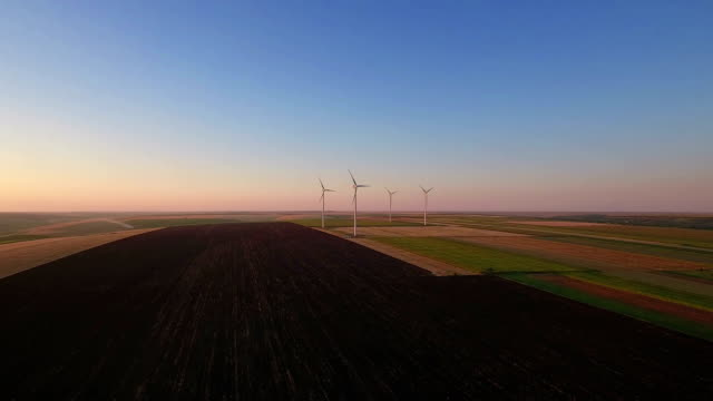 Aerial view of cluster of wind turbines in rural agriculture field. video