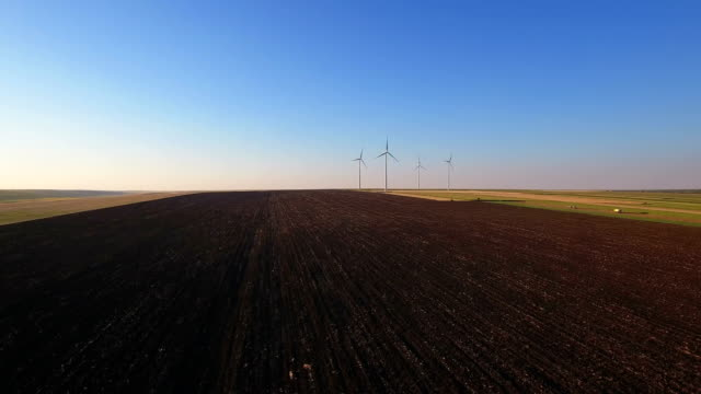 Aerial view of cluster of wind turbines in rural agriculture field video