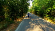 Aerial view of couple jogging along road in forest video