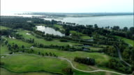 Aerial view of golf course with lake in the background video