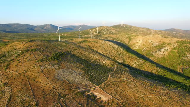 Aerial view of group of windmills on a hill path video