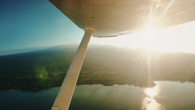 POV aerial view of island landscape at sunrise from small plane video
