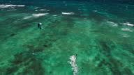 Aerial view of kitesurfer gliding across blue ocean video
