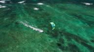 Aerial view of kitesurfers gliding across blue ocean video