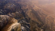 Aerial view of mountains with snow out of plane window 4k video