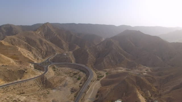 Aerial view of Muscat bay region, roads and crossroad (roundabout) in desert surrounded by mountains, Oman, sultanate on Arabian Peninsula, 4k UHD video