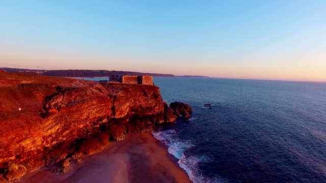 Aerial view of ocean and Nazare lighthouse at sunset, Portugal video