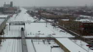 Aerial View of Passenger Train leaving City on a Winter Day video