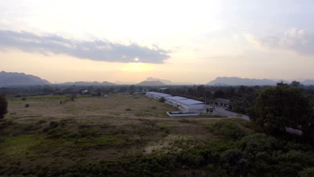Aerial view of remote village at sunset with beautiful mountain background, flyaway shot. video