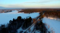 Aerial view of road through the woods along the frozen river in winter video