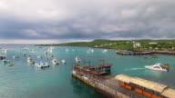 Aerial view of San Cristobal island coast, boats in harbour, Puerto Baquerizo Moreno harbor, Galapagos, Ecuador video