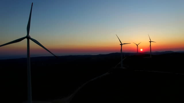 Aerial view of slowly rotating windmill blades at colorful sunset video