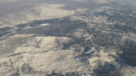 Aerial view of snow capped mountains out of plane window 4k video