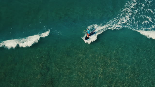 Aerial view of surfer stand up paddle boarding on blue ocean waves video