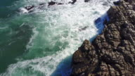 Aerial view of the rough seas crashing against the rocks video