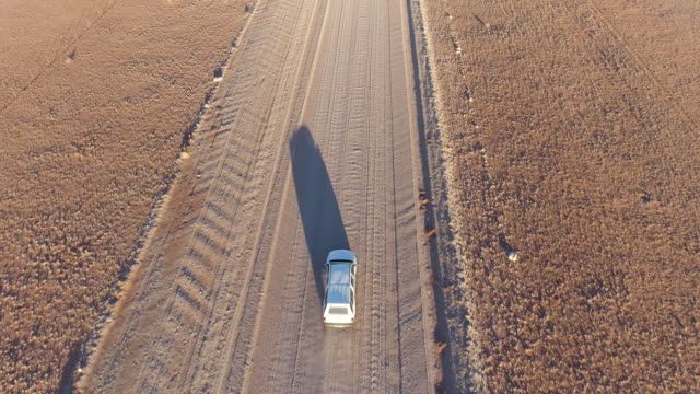 Aerial view of tourist vehicle driving on gravel road in the desert of Namibia video