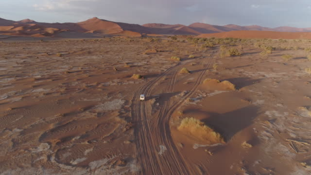 Aerial view of tourist vehicle driving through soft sand to Sossusvlei video
