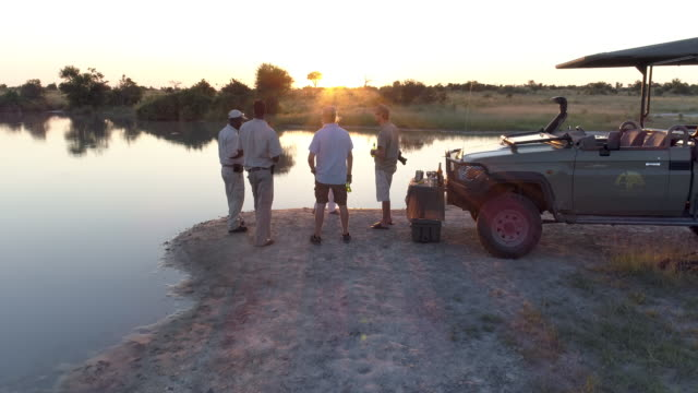 Aerial view of Tourists and guides enjoying a sundowner in the Okavango video
