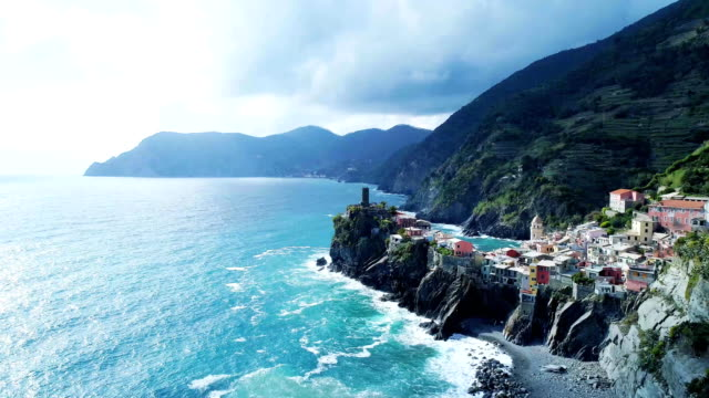 aerial view of travel landmark destination Vernazza, a small mediterranean sea town, Cinque terre National Park, Liguria, Italy. Afternoon sunny and cloud weather. 4k aerial drone side video shot video