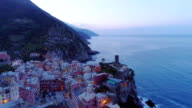 aerial view of travel landmark destination Vernazza, a small mediterranean sea town, Cinque terre National Park, Liguria, Italy. Before dawn blue hour night scene. 4k aerial drone orbit video shot video