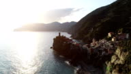 aerial view of travel landmark destination Vernazza, a small mediterranean sea town, Cinque terre National Park, Liguria, Italy. Sunset with cloud and flare. 4k aerial drone backward video shot video