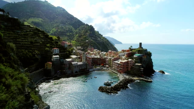 aerial view of travel landmark destination Vernazza, a small mediterranean sea town, Cinque terre National Park, Liguria, Italy. Morning sun and clouds. 4k slow motion 60 fps drone orbit video shot video