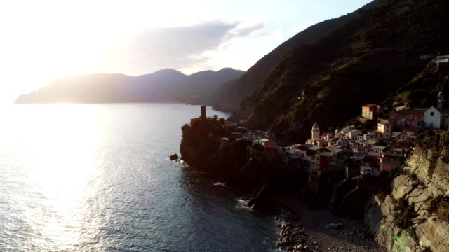 aerial view of travel landmark destination Vernazza, a small mediterranean sea town, Cinque terre National Park, Liguria, Italy. Sunset with cloud and flare. 4k aerial drone forward video shot video