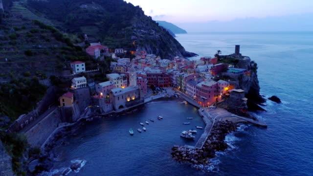 aerial view of travel landmark destination Vernazza, a small mediterranean sea town, Cinque terre National Park, Liguria, Italy. Before dawn blue hour night scene. 4k aerial drone forward video shot video