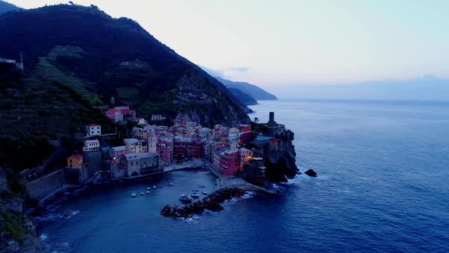 aerial view of travel landmark destination Vernazza, a small mediterranean sea town, Cinque terre National Park, Liguria, Italy. Before dawn blue hour night scene. 4k aerial drone orbit video shot video