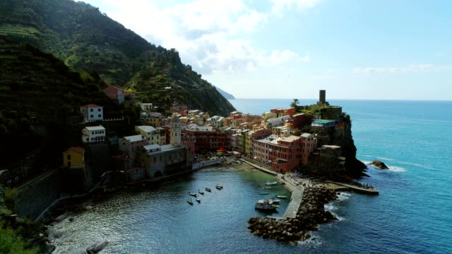 aerial view of travel landmark destination Vernazza, a small mediterranean sea town, Cinque terre National Park, Liguria, Italy. Morning with sun and clouds. 4k slow motion 60 fps drone orbit video video