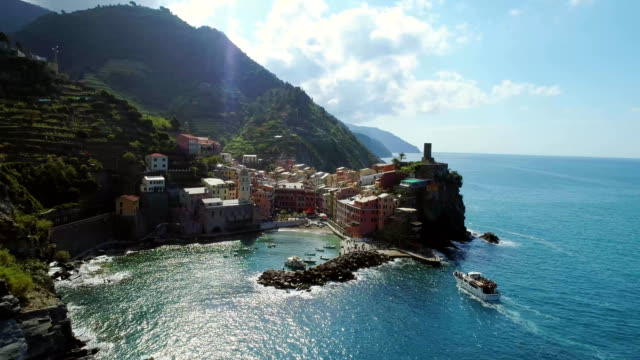 aerial view of travel landmark destination Vernazza,small mediterranean sea town, Cinque terre National Park, Liguria,Italy.Sunny, tourists boat approaching harbor. 4k drone forward video shot video