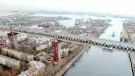 Aerial view of truss bridge above big river at the background of cityscape video