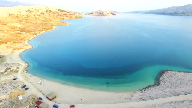 Aerial view of turquoise sea and yellow grass of Pag island, Croatia video