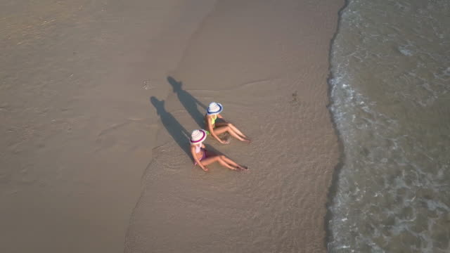 Aerial view of two young woman sunbathing on beach video