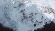 Aerial view of waves crashing over rock outcropping video
