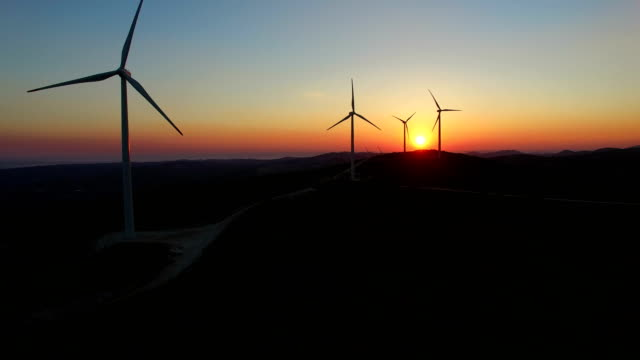 Aerial view of windmills at beautiful colorful sunset video