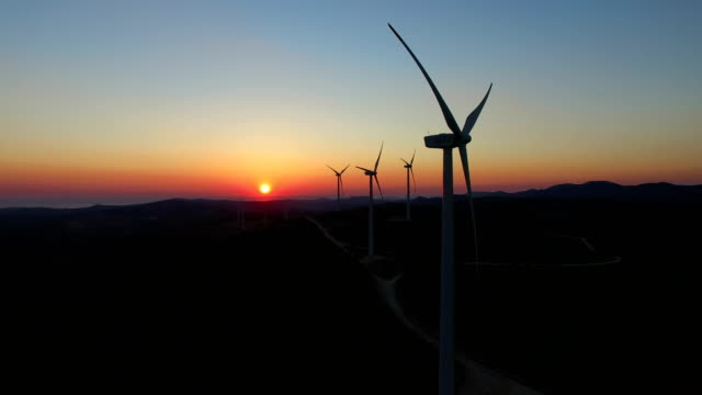 Aerial view of windmills with slowly rotating blades at sunset video