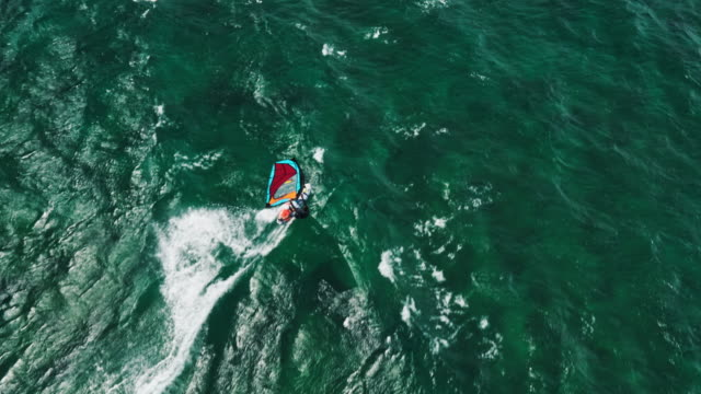 Aerial view of windsurfer gliding across blue ocean video