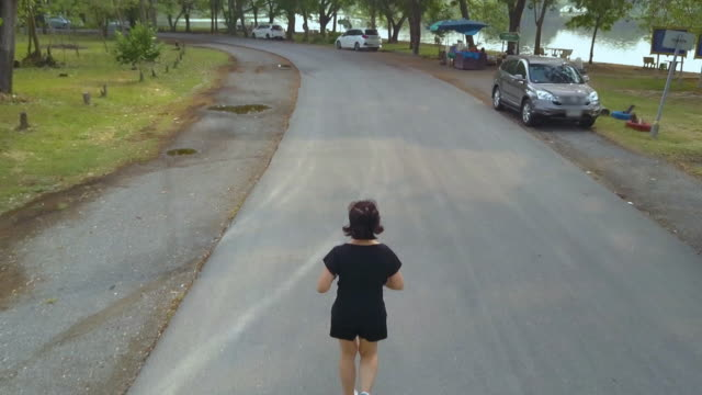 Aerial view of woman jogging in the park video