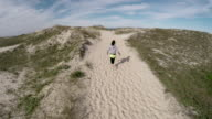 Aerial view of woman running through sandy dune area video