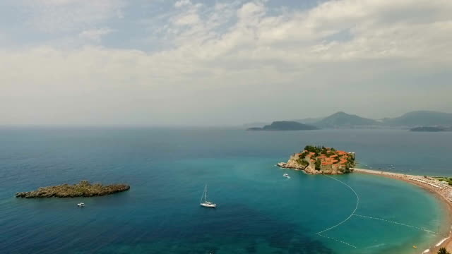 Aerial view of yacht niar small islet and resort in Montenegro video