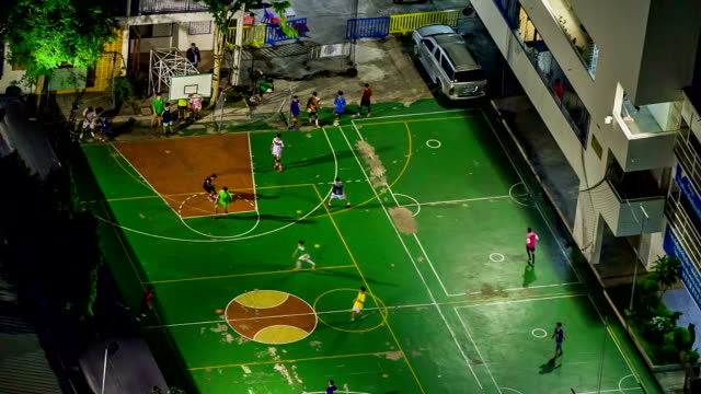 Aerial view of young boys playing football at small court video