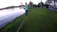 Aerial view of young man traversing slackline stretched above grasses, near lake video