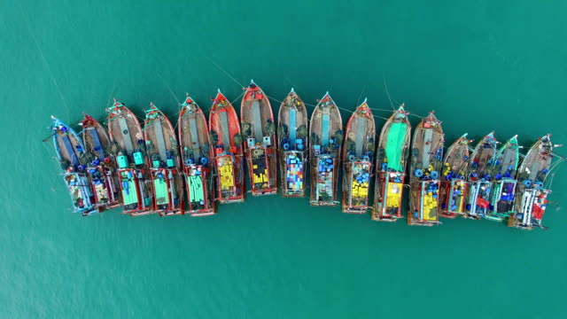 Aerial view on fishing boats are parked in one line at the pier. video