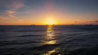 Aerial view over sea water, cargo ships and beautiful sunrise video