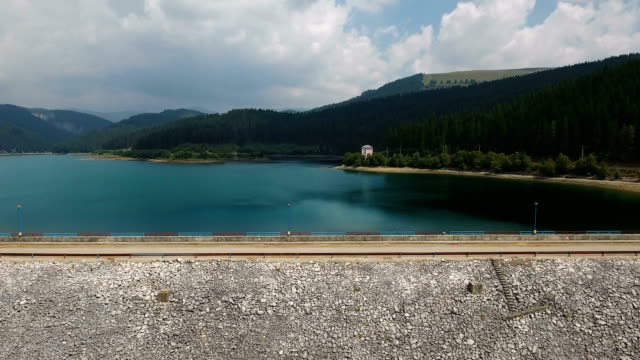 Aerial view over the dam of lake and flying slowly video